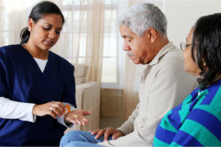 The caregiver gives medicine to the old man