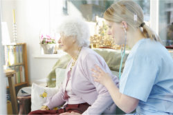 The caregiver helps the old woman to sit